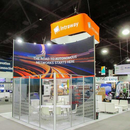 Intraway trade show booth with glass walls for private meeting room and large orange overhanging sign with logo