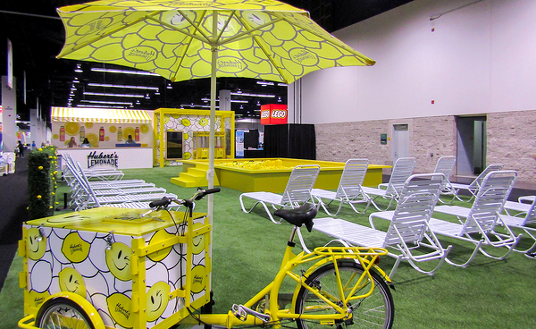 Hubert's lemonades trade show booth with lawn chairs, a sample booth, a bike with a cooler attached, and a ball pit pool